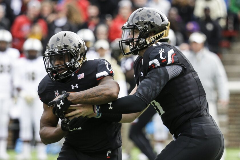 Cincinnati quarterback Gunner Kiel, right, hands off the ball to running back Hosey Williams in the first half of an NCAA college football game against UCF, Saturday, Oct. 31, 2015, in Cincinnati. (AP Photo/John Minchillo)