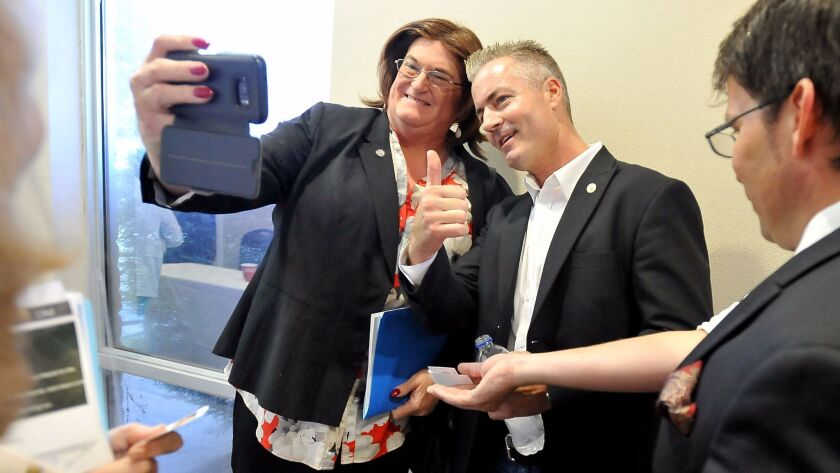 Republican gubernatorial candidate Travis Allen, right, poses for a photo with Gina Roberts, preside