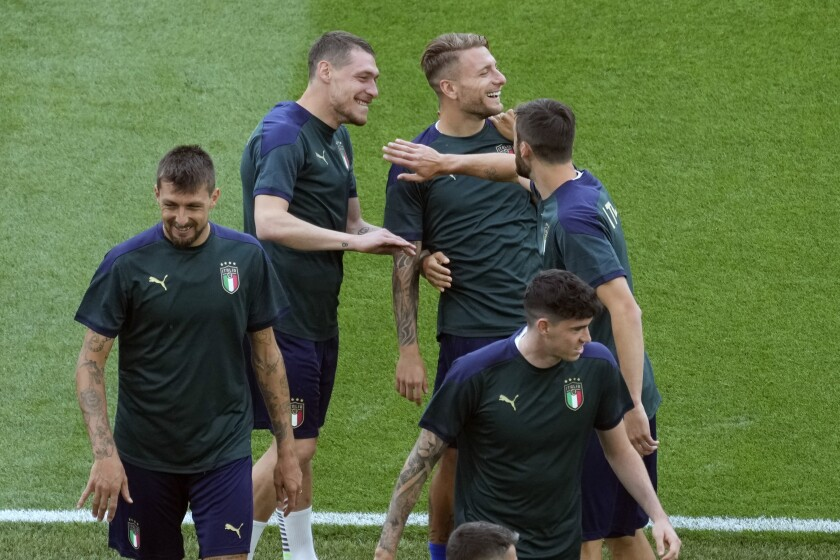 Italy's Ciro Immobile, top right, and Andrea Belotti, top left, smile during a training session ahead of Friday's Euro 2020, group A soccer match against Turkey, at the Rome Olympic stadium, Thursday, June 10, 2021. (AP Photo/Andrew Medichini, Pool)