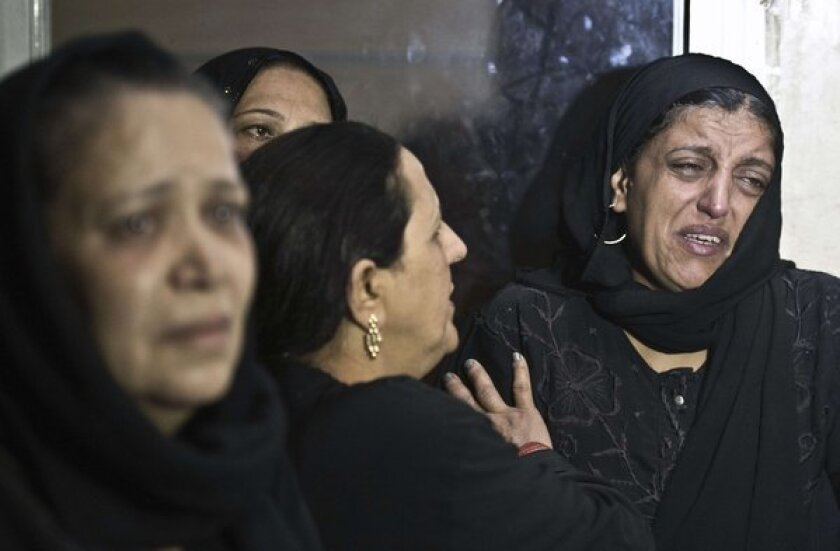 Egyptian women, some in tears, gather inside the Virgin Mary Coptic Christian church in Cairo after gunmen on a motorbike killed four people.