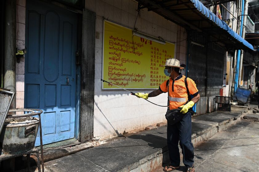 A city worker disinfects a street as a preventive measure against the coronavirus in Yangon, Myanmar.