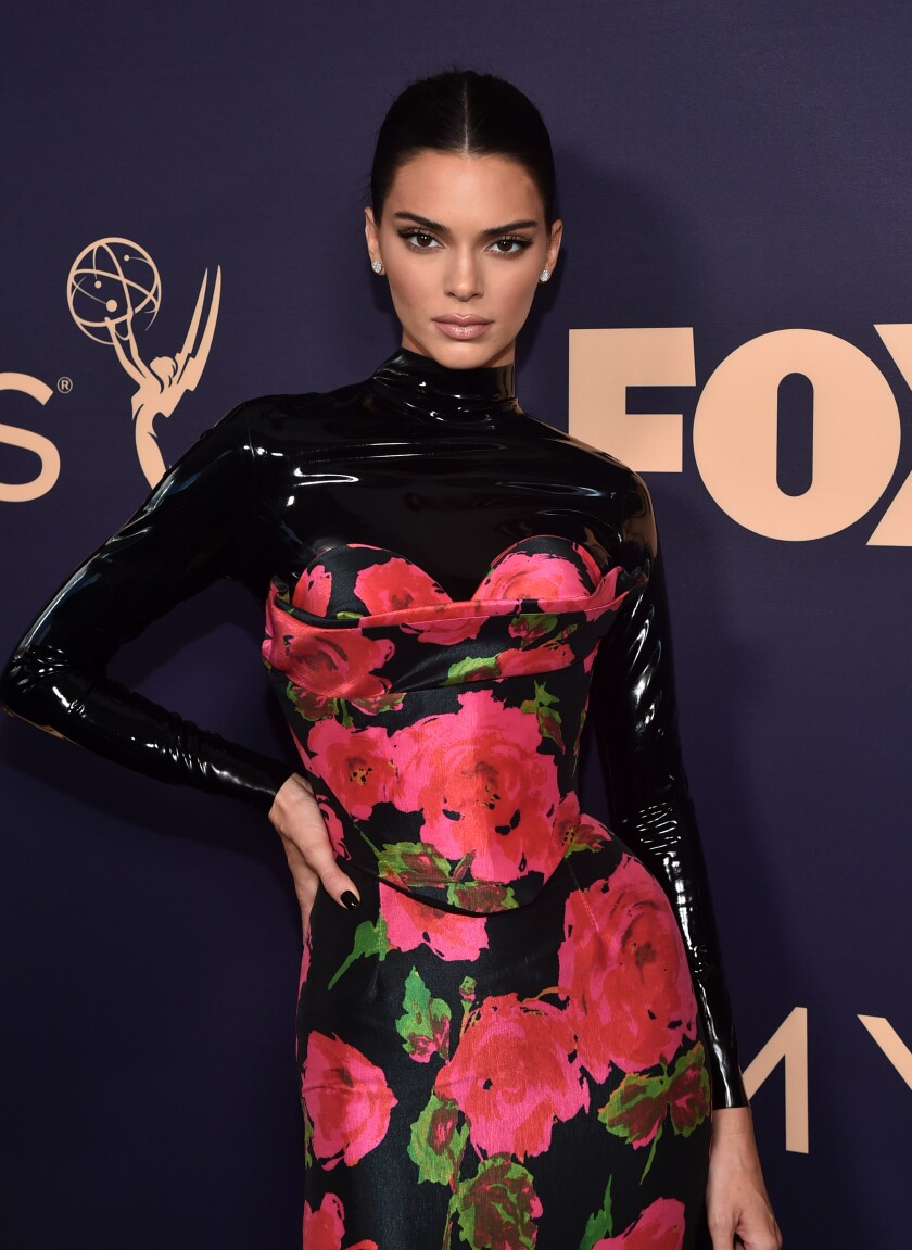 Kendall Jenner poses with her hand on her hip, wearing a latex and floral gown