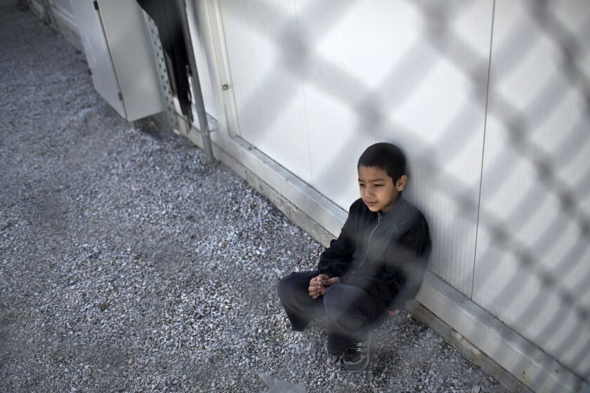 A boy sits inside an enclosure at the migrant and refugee registration camp in Moria, on the island of Lesbos, Greece, Thursday, Nov. 5, 2015.  The European Union predict that around 3 million more migrants are expected to arrive in the 28-nation bloc by the end of next year. (AP Photo/Marko Drobnj