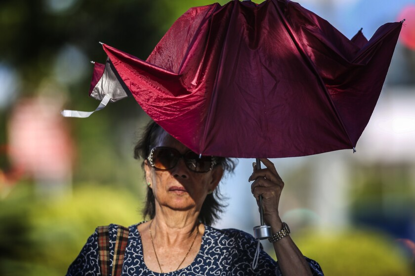 A woman uses a broken umbrella to shield herself from the sun in Los Angeles earlier this year.