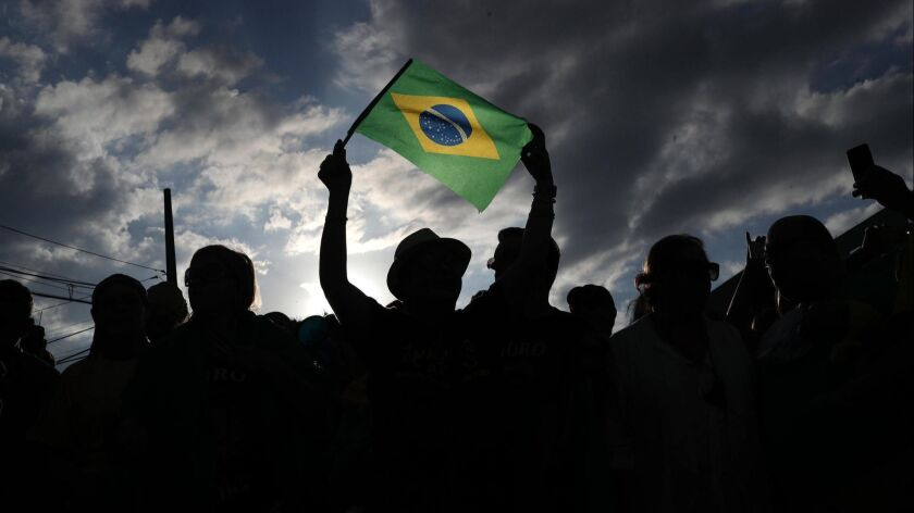 Anti-Lula demonstrators rally outside the federal police building in Curitiba, Brazil.