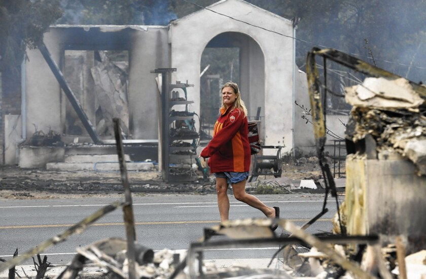 Iona Ridley, 45, wearing donated clothing, walks past the smoldering ruins of Middletown, Calif. She had abandoned her car as the Valley fire approached and was looking to retrieve it. Her home in Cobb Mountain, recently paid off, was destroyed.