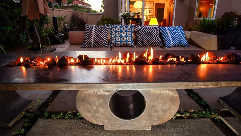 Lena Brion's custom-designed gas fire table is wide enough for dining on either side.