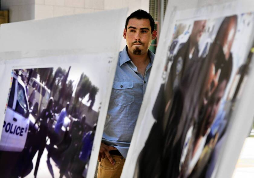 Victor Lopez, 21, a plaintiff in a federal lawsuit against the Compton Unified School District, stands near photos related to an incident in the suit. In the incident, school officers allegedly beat, pepper sprayed and used a chokehold on Lopez, who was taking video of an arrest on his iPod, and erased cellphone videos taken by students.