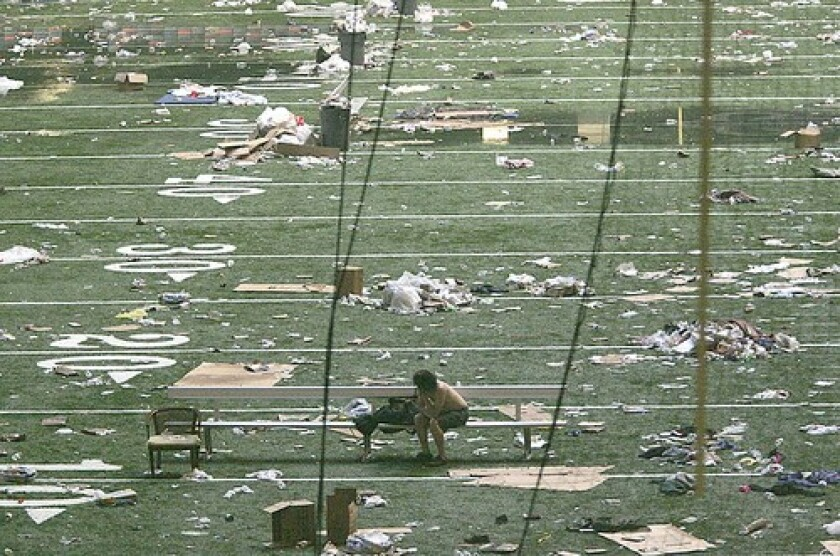 A lone evacuee sits on the field at the Superdome after Hurricane Katrina hit New Orleans in 2005.