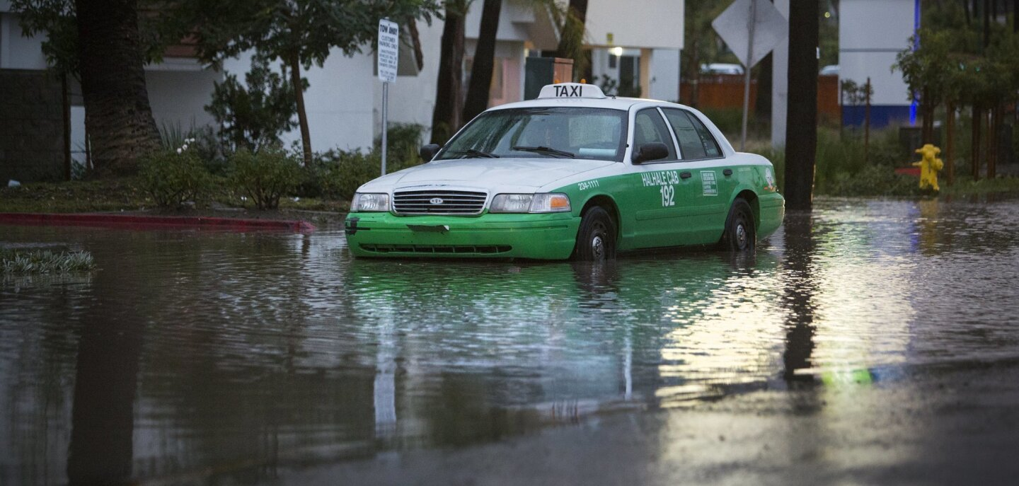 A taxi sits in standing water in the 500 block of Hotel Circle South in Mission Valley at about 5pm, Tuesday.