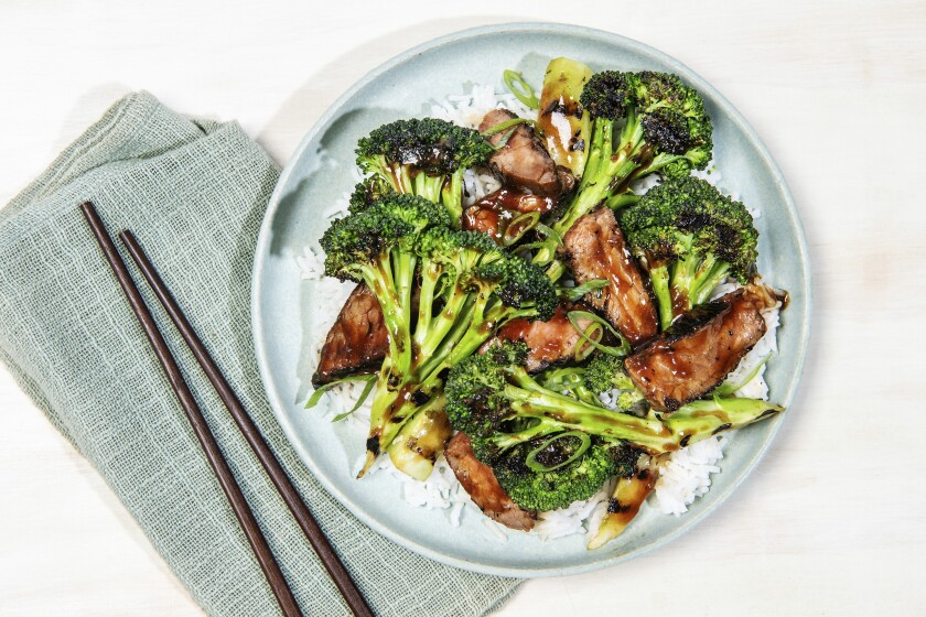 A plate of grilled broccoli and beef that has more vegetable than meat.