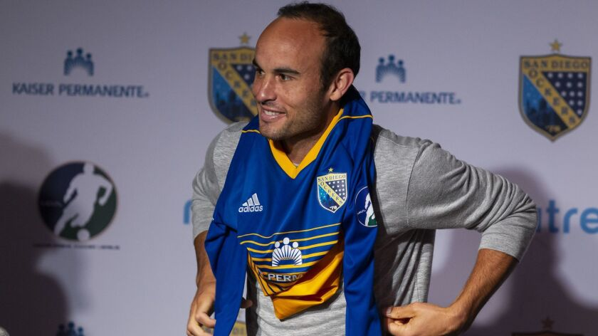 Landon Donovan puts on his Sockers jersey at Thursday's introductory news conference.