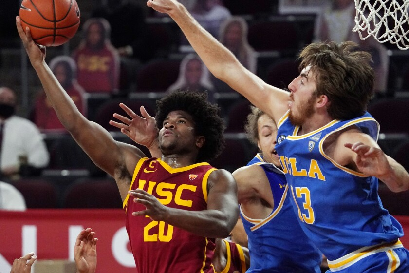 Southern California guard Ethan Anderson, left, shoots as UCLA guard Jake Kyman defends during the second half of an NCAA college basketball game Saturday, Feb. 6, 2021, in Los Angeles. (AP Photo/Mark J. Terrill)