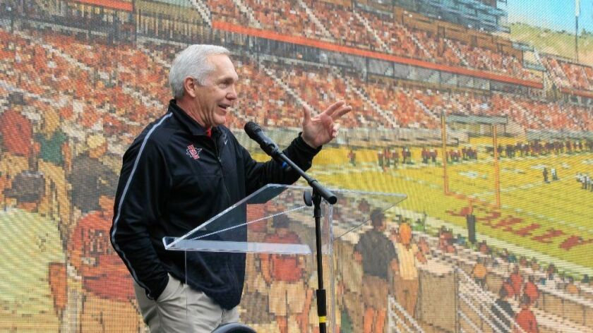At a Nov. 30 presentation, San Diego State football coach Rocky Long stands in front of an artist's drawing of the proposed Aztecs Stadium in Mission Valley.