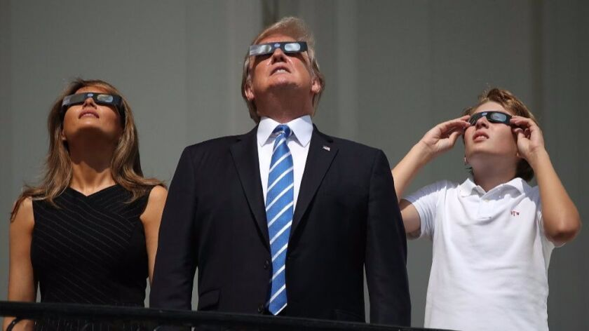 President Donald Trump, First Lady Melania Trump and their son, Barron, took in the eclipse on Monda