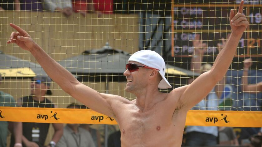 Jake Gibb raises his arms in celebration after winning the finals of the men's APV Huntington Beach Open with his partner Casey Patterson in May of 2016.