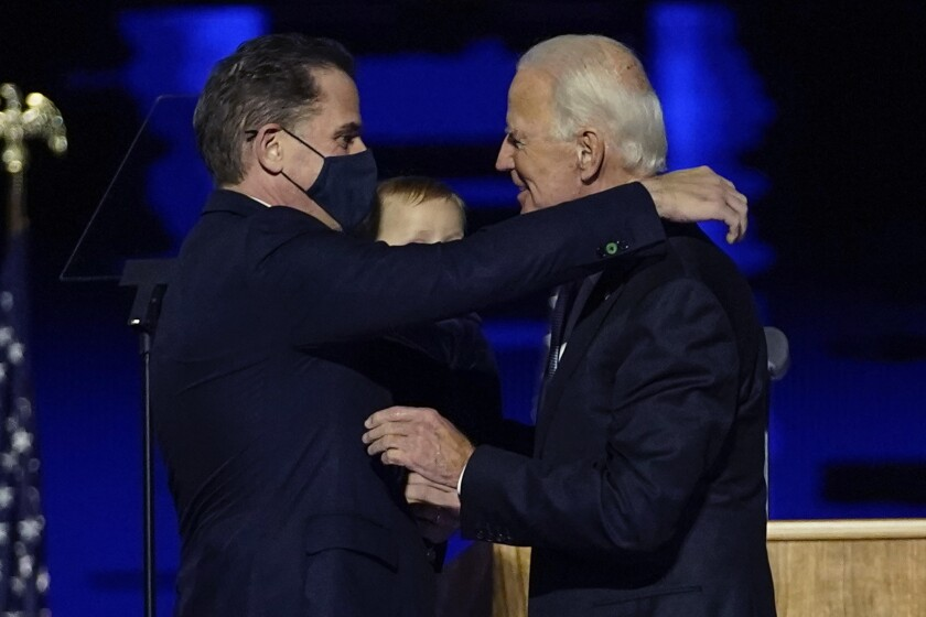 FILE - In this Nov. 7, 2020, file photo, President-elect Joe Biden, right, embraces his son Hunter Biden, left, in Wilmington, Del. Biden's son Hunter says he has learned from federal prosecutors that his tax affairs are under investigation. (AP Photo/Andrew Harnik, Pool)
