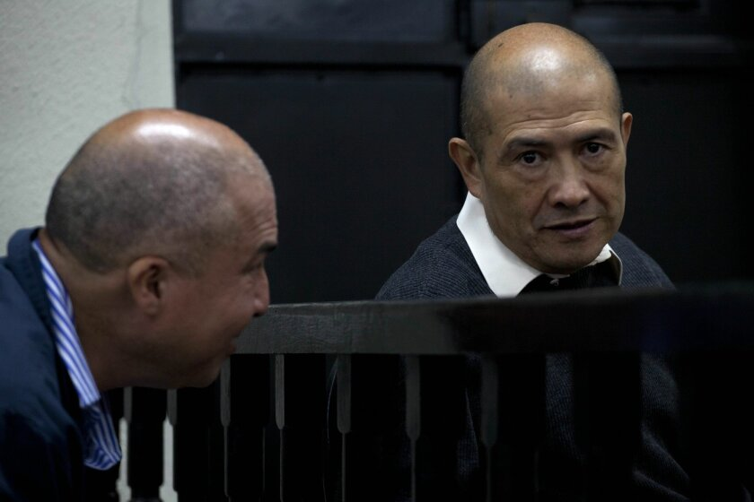FILE - In this March 13, 2014 file photo, ex-guerrilla Fermin Felipe Solano Barrillas, right, sits next to a relative during his trial in Chimaltenango, Guatemala. A Guatemalan court issued on Friday, July 4, 2014 the first conviction of Solano Barrillas for killings committed during the country's 1960-1996 civil war. The court has sentenced him to 90 years in prison for his role in the 1988 massacre of 22 pro-government farmers in the town of El Aguacate. (AP Photo/Moises Castillo, File)