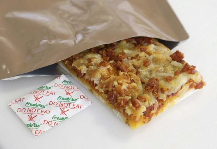 A slice of prototype pizza, in development to be used in military MREs (meals ready to eat), is shown in its packet with a smaller, freshness-keeping packet known as an oxygen scavenger. The pizza is being developed at the U.S. Army Natick Soldier Research, Development and Engineering Center in Natick, Mass.