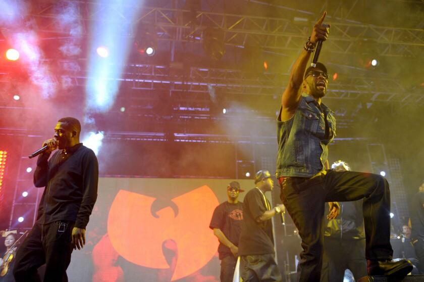 FILE - In this April 21, 2013, file photo, members of the Wu-Tang Clan perform on stage in front of their band logo at the Coachella Valley Music and Arts Festival at the Empire Polo Club in Indio, Calif. China has made a formal complaint to Canada over T-shirts with a similar bat-like logo ordered by a Canadian Embassy staffer in Beijing that allegedly mocked China's response to the coronavirus outbreak, in an apparent mix-up between the city of Wuhan and the hip-hop group. There are allegations the virus originated in bats and then spread to people in the city of Wuhan in late 2019. (John Shearer/Invision via AP)