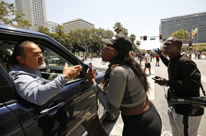 A passenger in a stopped vehicle argues with protesters