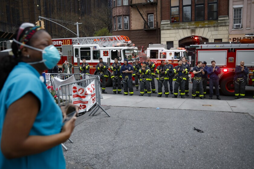 FILE - In this April 14, 2020, file photo FDNY firefighters gather to applaud medical workers as attending physician Mollie Williams, left, wears personal protective equipment due to COVID-19 concerns outside Brooklyn Hospital Center in New York. Essential workers are lauded for their service and hailed as everyday heroes. But in most states nurses, first responders and frontline workers who get COVID-19 on the job have no guarantee they'll qualify for workers' comp to cover lost wages and medical care. (AP Photo/John Minchillo, File)