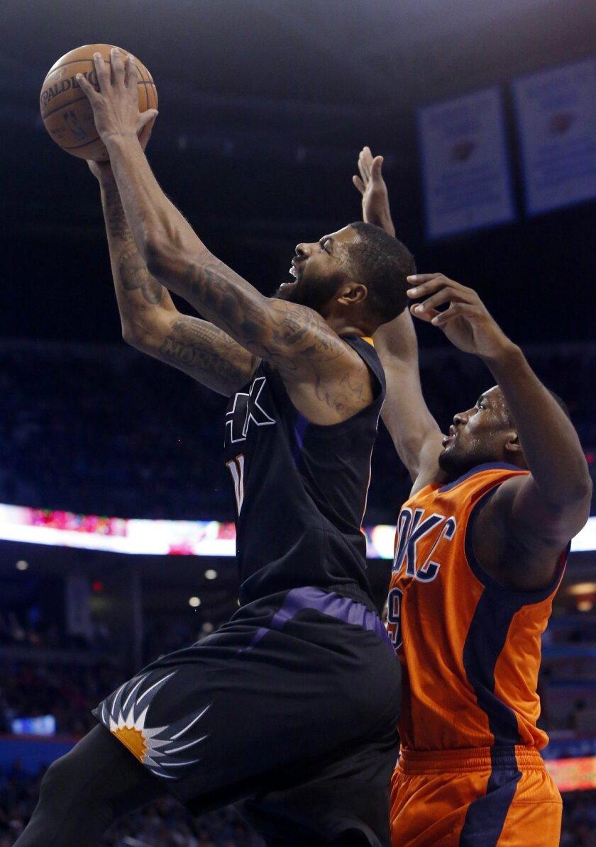 Phoenix Suns forward Markieff Morris (11) shoots in front of Oklahoma City Thunder forward Serge Ibaka in the first quarter of an NBA basketball game in Oklahoma City, Sunday, Nov. 8, 2015. (AP Photo/Sue Ogrocki)
