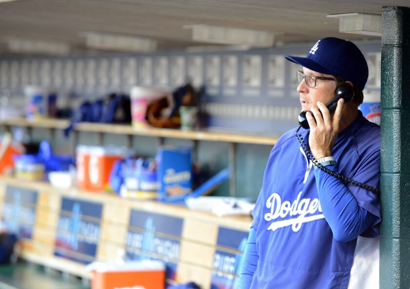 Dodgers bench coach Tim Wallach talks on the dugout phone during a July 8 game against Detroit.
