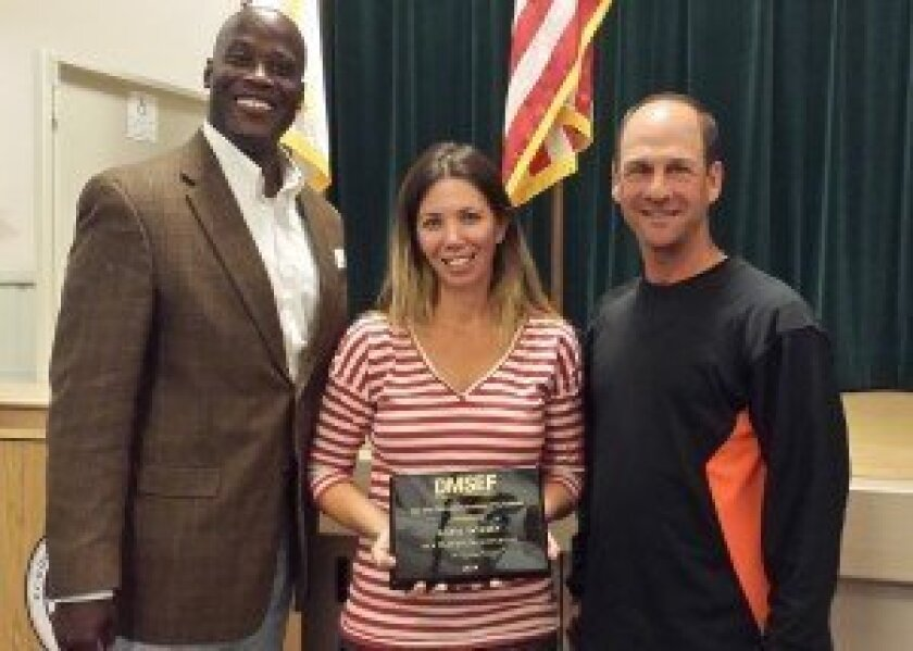 The Del Mar Schools Education Foundation's Ty Humes (VP marketing, at left) and Drew Isaacman (president, at right) present Katie Wilsey with a plaque in honor of her platinum level corporate affinity with the DMSEF.