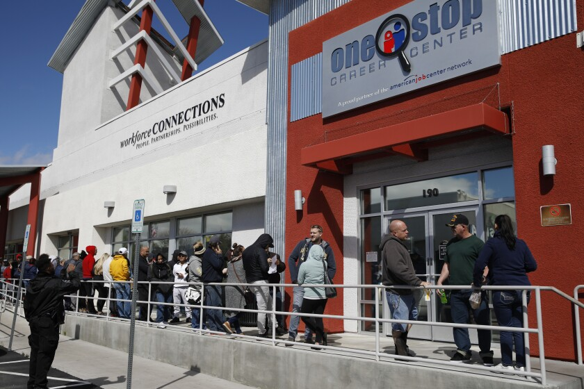 People in Las Vegas stand in line for help with unemployment benefits.