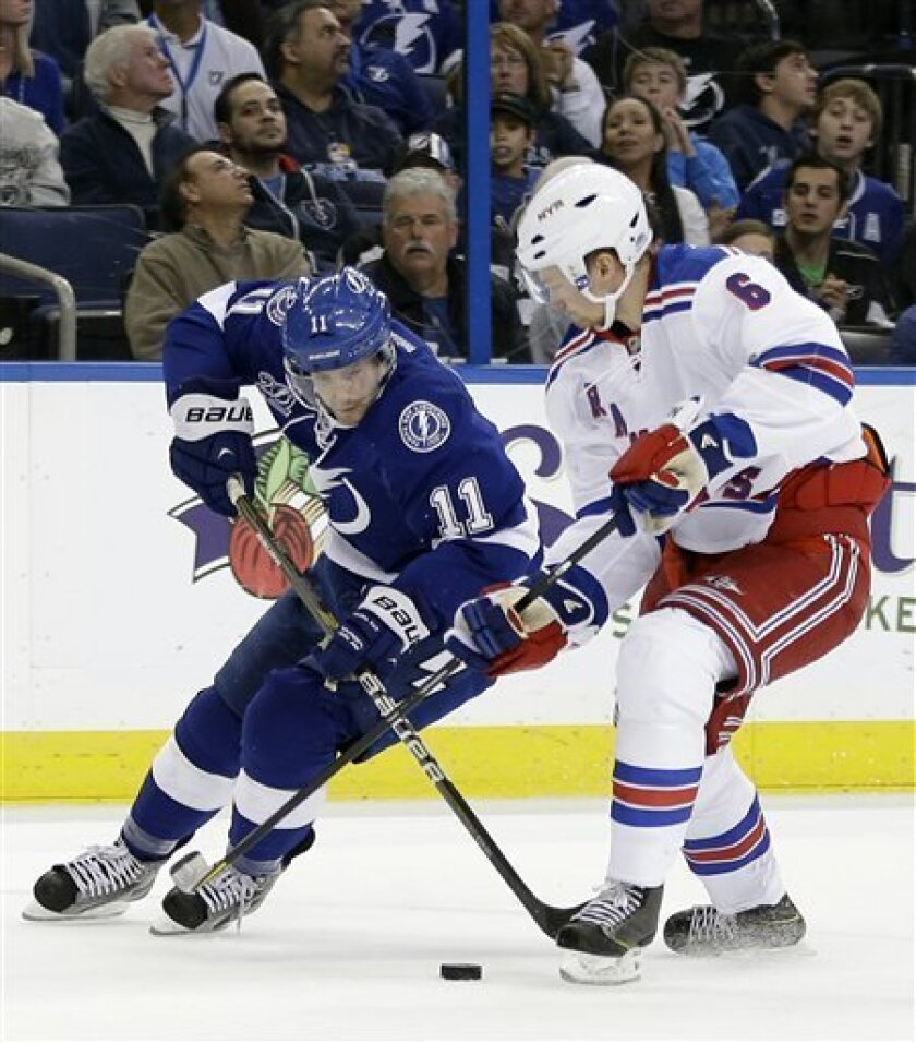 Tampa Bay Lightning center Tom Pyatt (11) batles with New York Rangers defenseman Anton Stralman (6), of Sweden, for a loose puck during the second period of an NHL hockey game on Saturday, Feb. 2, 2013, in Tampa, Fla. (AP Photo/Chris O'Meara)