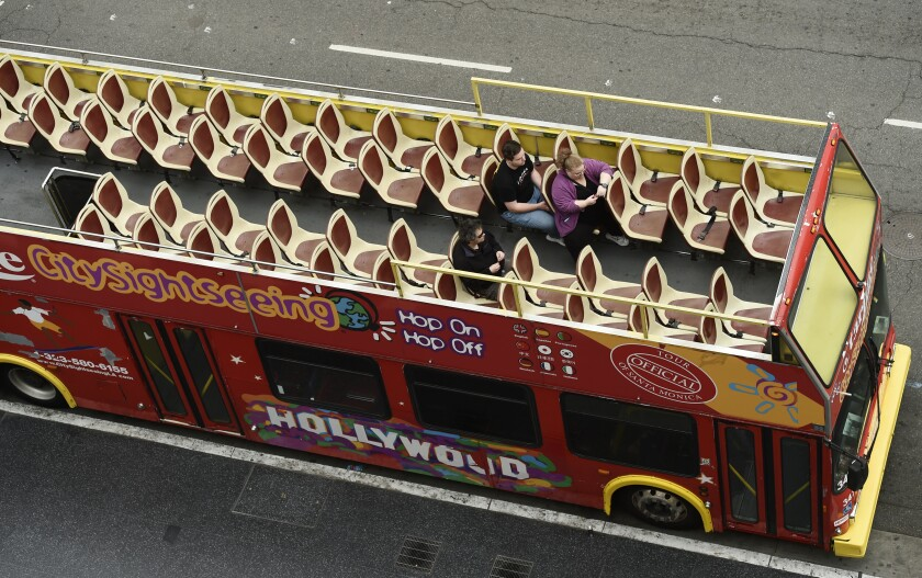 Passengers sit in a mostly empty sightseeing bus on Hollywood Boulevard, Thursday, March 12, 2020, in the Hollywood section of Los Angeles. (AP Photo/Chris Pizzello)