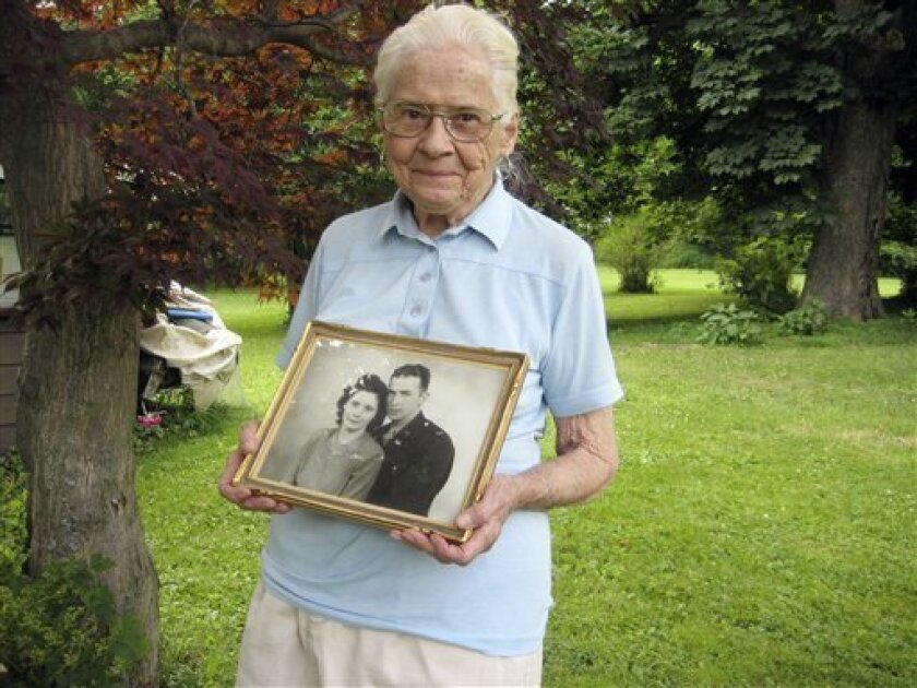 FILE - In This June 25, 2010 file photo, Jean Stevens, 91, holds a photograph from the 1940s of herself and her late husband, James, outside her home in Wyalusing, Pa. Stevens who lived with the corpses of her husband and twin sister until authorities found out and took them away, recently hired workmen to build the vault and plans to keep her loved ones there. (AP Photo/Michael Rubinkam, File)