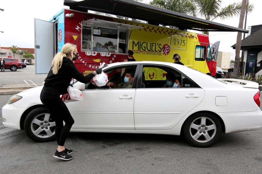 Strut Bar & Club event director Venessa Lynn, left, gives multiple lunches in two bags to Rafael Lopez and his children, of Costa Mesa, during Wednesday's free meals event.