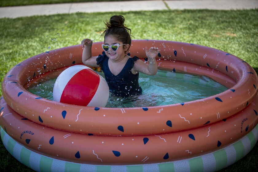 Child plays in a kiddie pool in front of her Whittier apartment