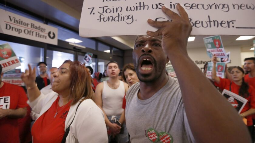L.A. teachers union Vice President Cecily Myart-Cruz, left, and parent Todd Tyson lead chants during a recent rally in the lobby of L.A. Unified headquarters just west of downtown.