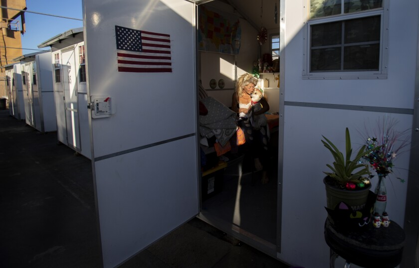 Karen Morea, 62, hugs her dog Jack-Jack inside her tiny village home in a parking lot adjacent to a Riverside shelter