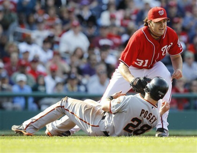 Washington Nationals pitcher John Lannan (31) tags out San Francisco Giants' Buster Posey on a run down during the fourth inning of an MLB baseball game, Saturday, April 30, 2011 in Washington. (AP Photo/Luis M. Alvarez)
