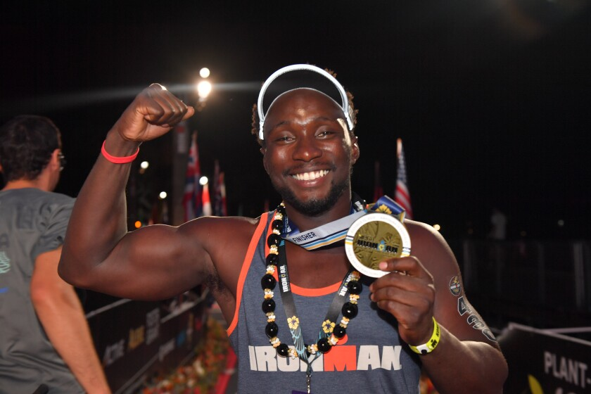 Roderick Sewell, 27, holds his medal after finishing the 2019 Ironman World Championship in Hawaii on Oct. 12. He is the first above-the-knee double-amputee to finish the race on prosthetic legs.