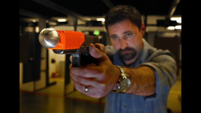 "Christian Ellis of Alternative Ballistics demonstrates his company's ""less lethal"" weapon at the San Diego Firearms Training Center in Poway, Calif. When fired, the pistol's bullet is captured inside a metal sphere, which is propelled at a lower velocity than a bare bullet."