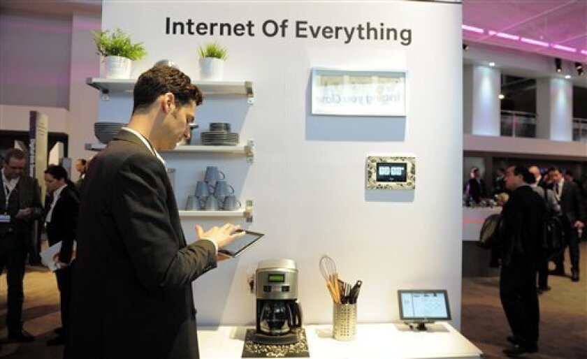 """In this Tuesday, Feb. 26, 2013, photo, a man checks his device in front of a banner """"Internet of Everything"""" at the Mobile World Congress, the world's largest mobile phone trade show, in Barcelona, Spain. The first wave of the wireless revolution was getting people to talk to each other through cel"""