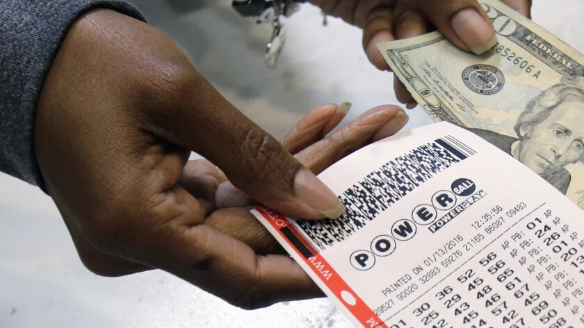 FILE - In this Jan. 13, 2016 file photo, a clerk hands over a Powerball ticket for cash at Tower Cit