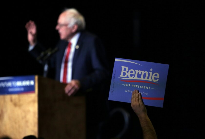 A supporter, at right, holds a sign as Democratic presidential candidate, Sen. Bernie Sanders, I-Vt., left, speaks during a rally Friday, Feb. 19, 2016, in Reno, Nev. (AP Photo/Marcio Jose Sanchez)