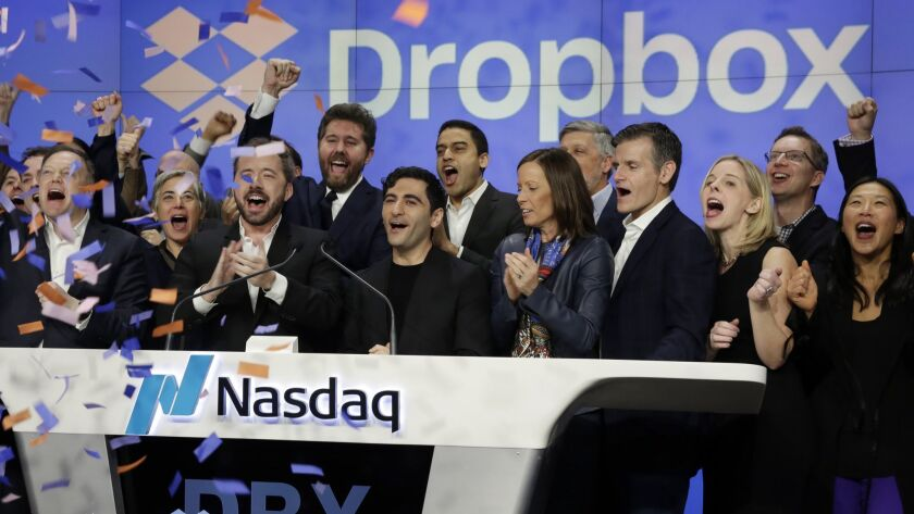 Dropbox executives, celebrating the company's IPO, ring the opening bell at the Nasdaq MarketSite in New York's Times Square.