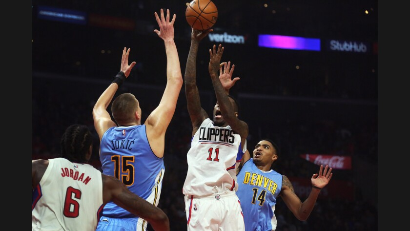 Clippers guard Jamal Crawford goes up for a shot as Denver Nuggets forward Nikola Jokic and guard Gary Harris converge on Dec. 26.