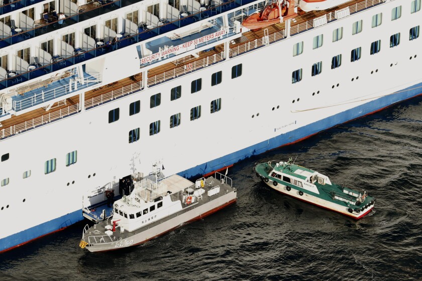 A Japanese coast guard patrol boat, left, ties up alongside the cruise ship Diamond Princess to take passengers who tested positive for the coronavirus to hospitals off Yokohama on Wednesday.