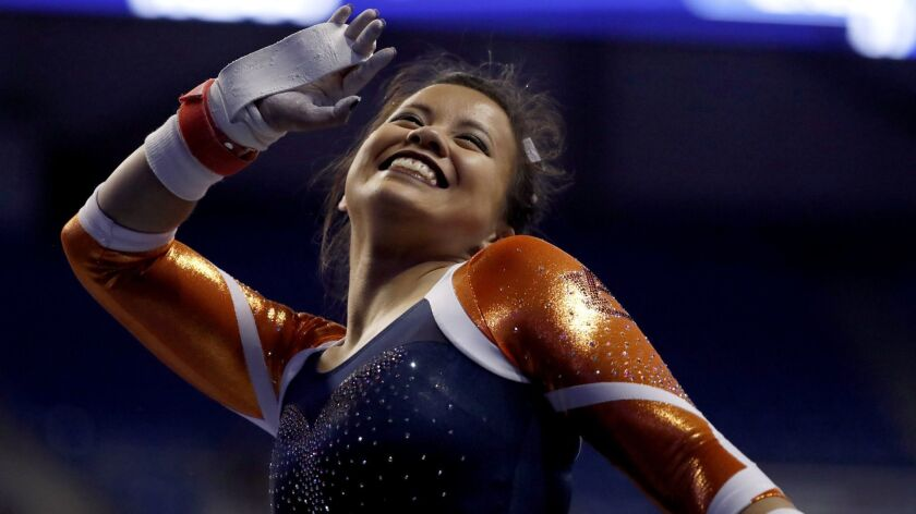 Auburn's Samantha Cerio smiles and signals to the crowd before competing on the uneven parallel bars