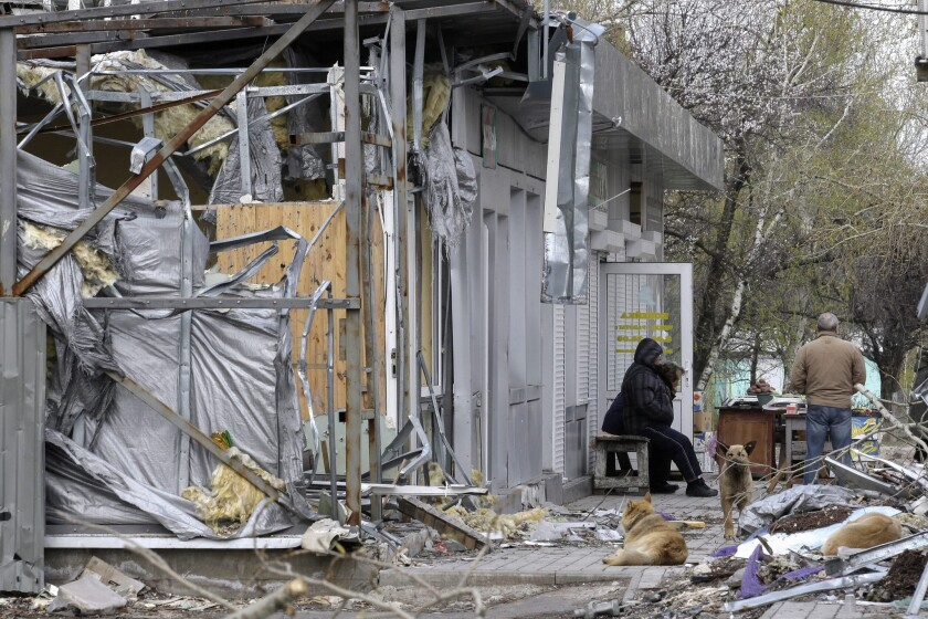 People and animals on Wednesday amid the debris of March shelling in a village near the Donetsk airport.