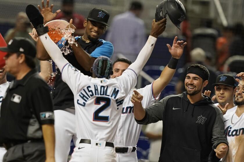 Jugadores de los Marlins de Florida celebran la varrera de la victoria anotada por Jazz Chisholm Jr. (2) en el 10mo inning de su juego de béisbol contra los Nacionales de Washington, el lunes 20 de septiembre de 2021 en Miami. (AP Foto/Marta Lavandier)