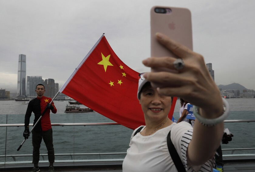 In this Saturday, Aug. 17, 2019 file photo, pro-China supporters take a selfie with a Chinese national flag to support police and anti-violence during a rally at a park in Hong Kong.